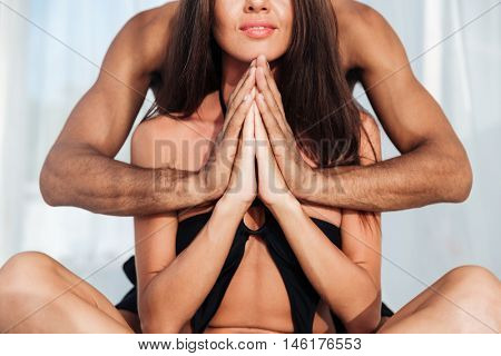 Cropped position of a beautiful multiracial couple mediating together and sitting in lotus position on the beach be