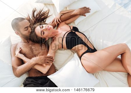 Image of happy multiracial couple laying at the white beach bed and kissing