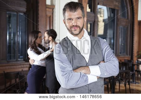 Confident Man With Arms Crossed Standing While Dancers Performin