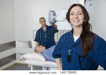 Doctor Smiling While Colleague Taking Patient's Xray