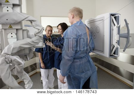 Smiling Radiologists Using Tablet Computer While Standing By Pat
