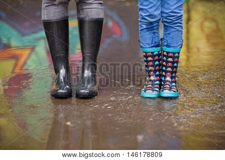 Kid boy and woman in funny rubber boots standing in the puddle in the street after rain. Family in colorful rubber boots in a big puddle with graffiti reflections - having fun after rain. Outdoor.
