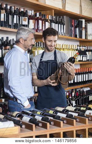 Salesman Removing Wine Bottle From Bag For Customer