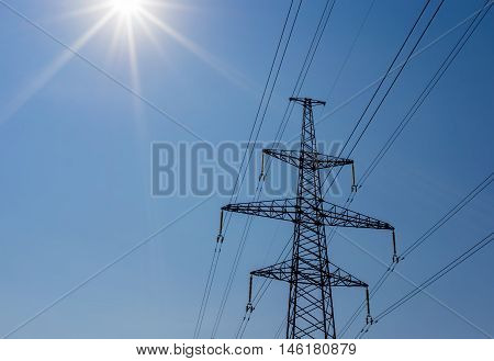 modern electricity pylon and the sun's rays - space for text