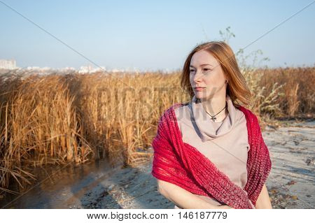 Red-haired woman with a red shawl on the waterfront