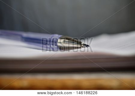 Detail of a sharp tip of the blue ball pen on the white lined notepad as a symbol of business office stationary