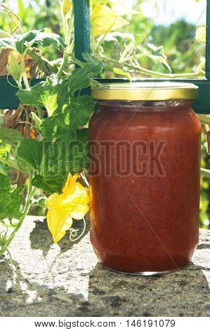 Full large jar with a red homemade quince jam