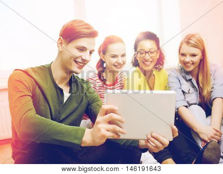 education and technology concept - smiling students making picture with tablet pc computer at home