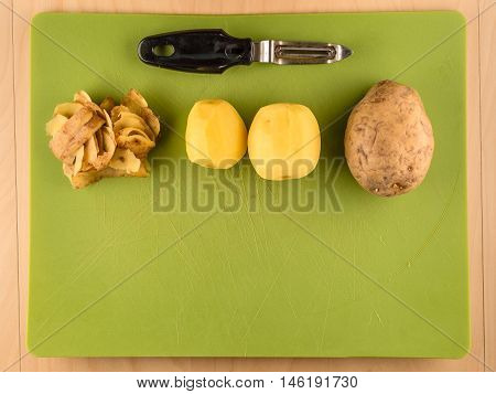Two unpeeled and one peeled potatoes with skins on green plastic board with peeler, simple food preparation illustration, vegetarian dieting, top view still life with bottom half copyspace