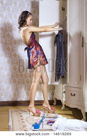 beautiful young woman looks on dress near opend white wardrobe