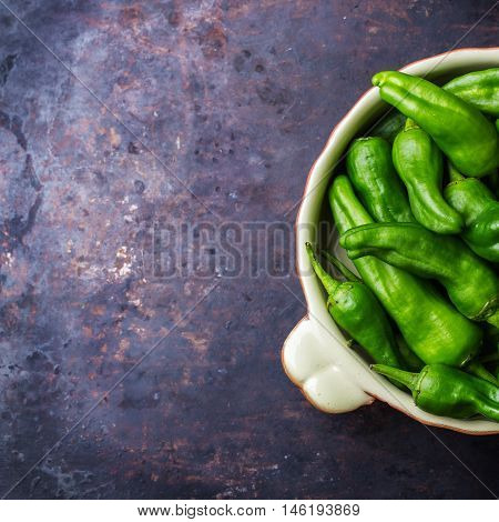 Food and drink, still life, moody concept. Raw green peppers pimientos de padron traditional spanish tapas on a black rusty table. Selective focus top view flat lay copy space background