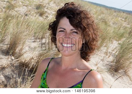 Portrait Of Smiling 40-year-old Brunette Woman At Beach