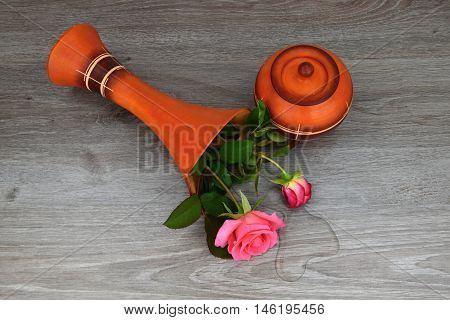 Capsize flower vase with roses. The vase is a wooden base. Water leaked out of a vase.