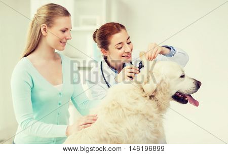 medicine, pet, animals, health care and people concept - happy woman and veterinarian doctor with otoscope checking up golden retriever dog ear at vet clinic