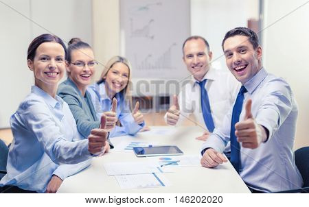 business, success, technology and office concept - smiling business team with tablet pc computer and papers showing thumbs up in office