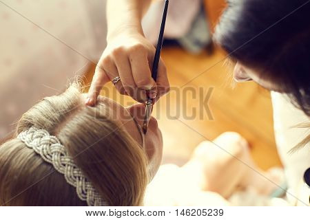 Beautiful bride portrait wedding makeup. Young beautiful bride applying wedding make-up by professional make-up artist