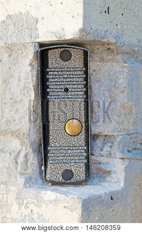 the intercom button in the wall of the house