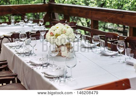 Floral arrangement of white flowers at the wedding table. Beautiful wooden chairs. The bouquet is to decorate with books.