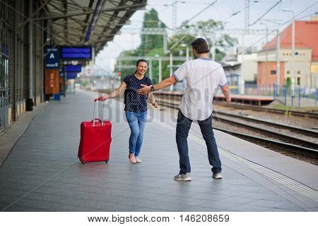 At an empty platform flee a young woman with a red suitcase. Joyful smile on her face. The young man meets her. He's ready to hug a woman.