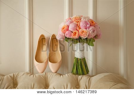 bridal bouquet of peones wedding flowers for the ceremony with white shoes
