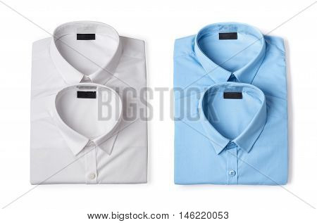 Two folded blue and two white new men's shirts close-up isolated on white background