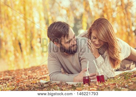 Young couple in love sitting on a fallen autumn leaves under a tree in a park drinking an ice tea and enjoying a wonderful autumn day. Focus on a man