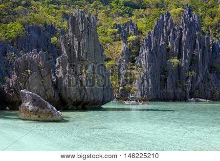 Landscape with filippino boat, rocks and blue bay. El Nido, Palawan island, Philippines