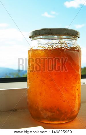 Glass jar filled with jam amber color