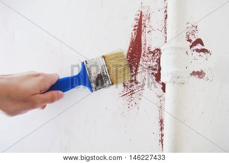 Hand holding a brush painting wall in white color behind radiator at the apartment room. Renewals repairs background.