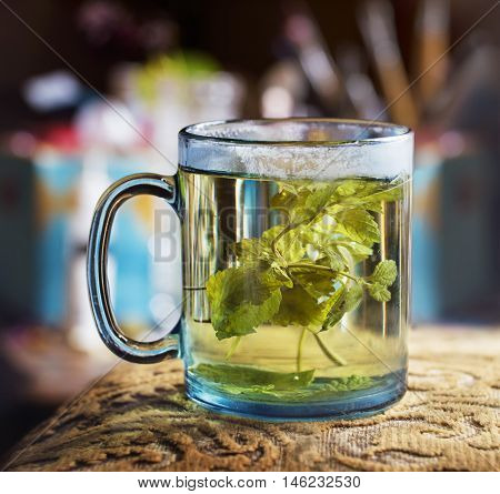 Blue transparent glass of hot tea with lemon balm (Melissa) and steam on a glass edge
