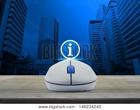 Wireless computer mouse with information sign icon on wooden table over city tower background