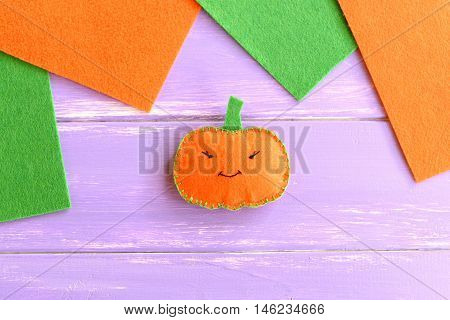 Halloween pumpkin ornament, orange and green felt pieces on wooden background with blank place for text. Halloween art craft for children. Home made felt pumpkin decor