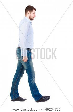 Back view of walking businessman. Bearded businessman in white shirt. It goes sideways.