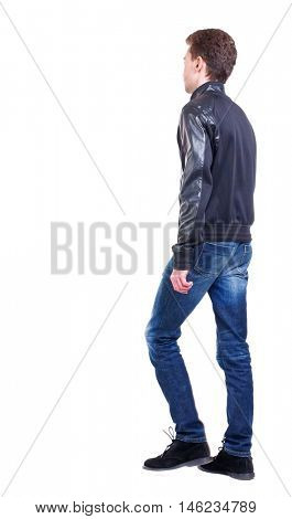 Back view of going handsome man. walking young guy . Isolated over white background. Curly guy in a black leather jacket goes sideways.