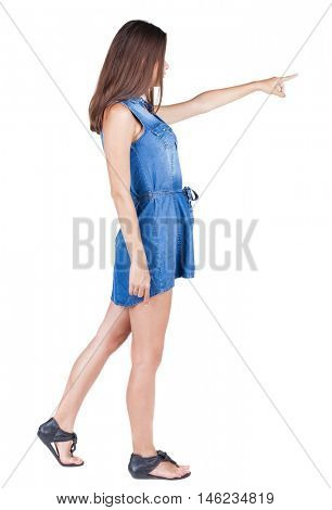 Back view of young leggy woman pointing. beautiful girl in dress. Rear view people collection. backside view of person. Isolated over white background.