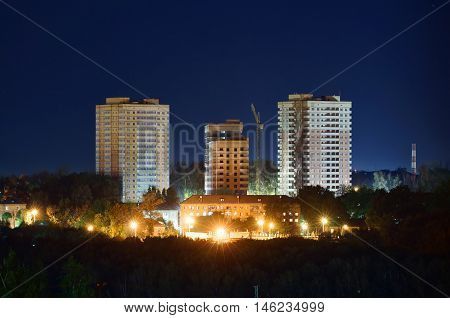 View on construction of residental buildings in Tula with street lights in summer evening, Russia.