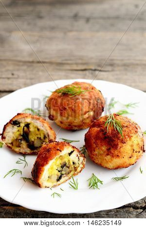 Fried meat cutlets stuffed with cheese and fried mushrooms on plate on wooden background. Home cutlets prepared from minced meat. Closeup