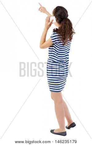 back view of standing young beautiful woman using a mobile phone. Swarthy girl in a checkered dress shows a finger and talking on the phone.