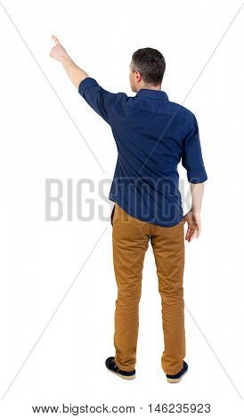 Back view of pointing business man. man in a blue shirt with the sleeves rolled up showing up with his right hand.