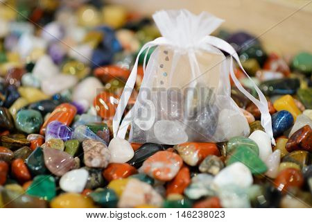 Bag of colored stones. Idea for the Gift of stones. Round precious and semi-precious minerals. Polished minerals. Beautiful natural stones. Natural stones. Geology and geography. Scattering of stones.