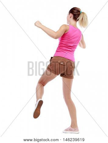 back view of woman funny fights waving his arms and legs. Isolated over white background. Sport blond in brown shorts hit someone