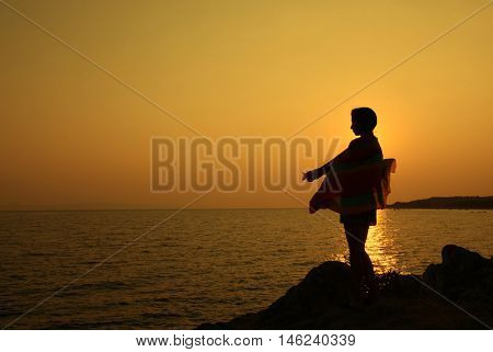 Girl is standing on seaside during beautiful sunset