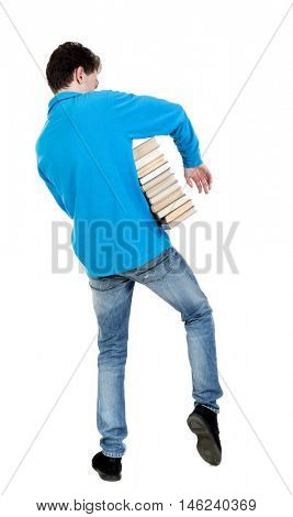 A man carries a heavy pile of books. back view. curly-haired student in a blue warm jacket came out of the library.