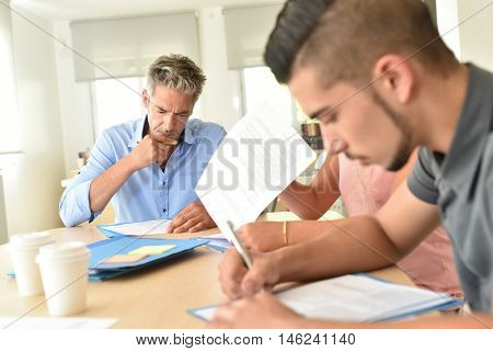 College students filling in registration forms