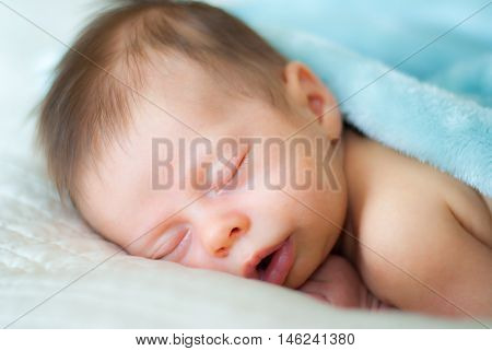 Newborn Baby Boy Sleeping on White Blanket