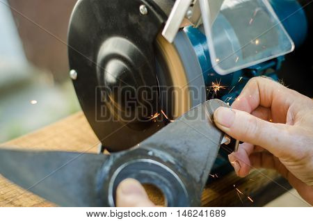 Worker sharpening his blade lawn mower. Flying sparks and work go well.