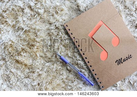 Notebook with pen on brown shaggy carpet