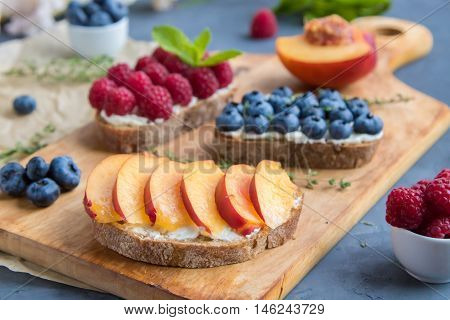 Sandwiches with mild cream cheese and different berries on carving board