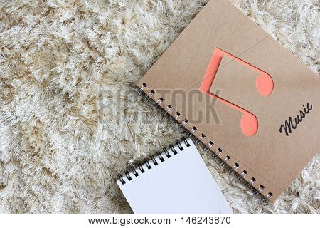 notebook with Blank notepad on brown shaggy carpet