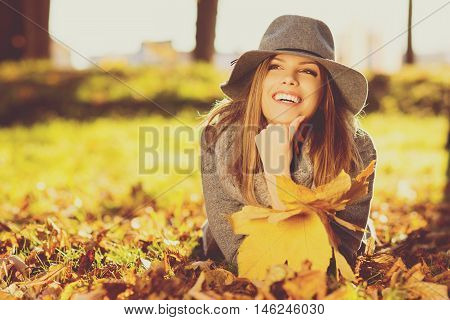 Young woman in park on sunny autumn day, smiling, holding leaves. Cheerful beautiful girl in gray sweater and floppy hat outdoors. Retouched, matte filter applied, back lit, natural light.